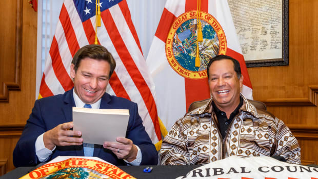 Florida Gov. Ron DeSantis, left, signs a gaming compact with Marcellus Osceola Jr., chairman of the Seminole Tribe of Florida, that will allow the tribe to build three more casinos and to hold exclusive rights to sports betting, roulette and craps in the state. The deal was ratified May 19, 2021 by the state Legislature. (Photo by Colin Hackley for the Seminole Tribe of Florida)