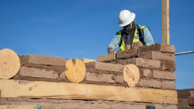 Community construction worker laying adobe brick on the renovated home. (Photo courtesy of Herman Sanchez, Kewa Pueblo)