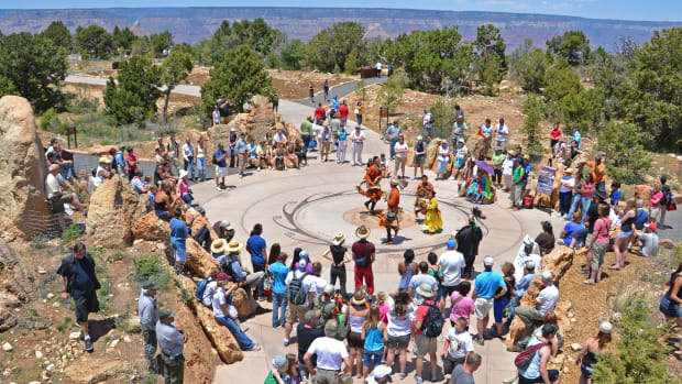 Visitors watch as Pollen Trail Dancers perform a traditional dance at the Landmark and Tribal Medallion near Mather Point at the Grand Canyon in 2011. The number of visitors to the Grand Canyon National Park in Arizona fell from 6 million in 2019 to 2.9 million in 2020, the biggest drop of all the national parks. Tribes and tribal citizens manage tours, create and sell art, and operate hotels, restaurants, and gift shops. (Photo by Michael Quinn, National Park Service)