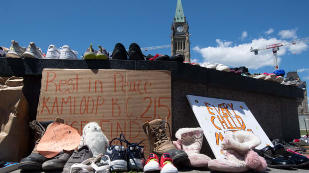 Shoes sit on the eternal flame on Parliament Hill in Ottawa, Canada, on Monday May 31, 2021, after the remains of 215 children were found at the site of a former Indian residential school in Kamloops, British Columbia. Canada has now declared Sept. 30 a Day of Truth and Reconciliation, a national holiday, to remember those who suffered at the schools. The United States holds a Remembrance Day as well on Sept. 30. (Adrian Wyld/The Canadian Press via AP)