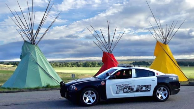 Crow Nation tribal police car parked in front of teepees. (Facebook via Crow Tribal Police Department)