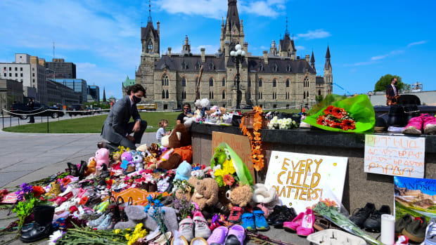 Canadian Prime Minister Justin Trudeau visits a memorial at the Eternal Flame on Parliament Hill in Ottawa on Tuesday, June 1, 2021, that's in recognition of discovery of children's remains at the site of a former residential school in Kamloops, British Columbia. (Sean Kilpatrick/The Canadian Press via AP)
