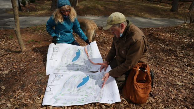 Belle Ragins and Erik Thelen, who live near the site of Kohler Co.'s proposed golf course in Sheboygan, Wis., examine a map prepared by environmental engineer Roger Miller, who chairs the town of Wilson Plan Commission. The map overlays the project with present lake levels, showing several planned features under water due to erosion and fluctuating water levels along Lake Michigan's shoreline. Photo taken April 27, 2021. (Photo by Dee J. Hall, Wisconsin Watch)