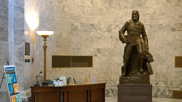 A statue of Marcus Whitman stands next to a visitors' information desk in the Legislative Building at the Capitol in Olympia, Wash., Wednesday, May 12, 2021. For generations, Whitman has been viewed as an iconic figure from early Pacific Northwest history, a venerated Protestant missionary who was among 13 people killed by the Cayuse tribe near modern-day Walla Walla, Washington, in 1847. But this past year has seen the continued reappraisal of Whitman, whose actions are now viewed by many as imperialistic and destructive, and the Washington Legislature voted to remove a similar statue of Whitman from Statuary Hall in Washington, D.C. (AP Photo/Ted S. Warren)