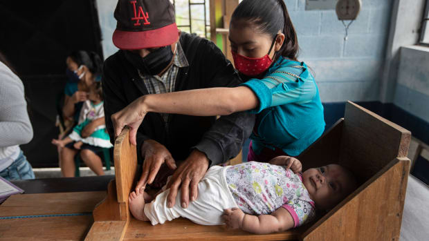 Volunteer Santiago Sanchez, left, measures the height of a baby boy alongside the baby's mother at a health center in Cachoche village near Tizamarte, Guatemala, Thursday, Dec. 10, 2020. A nurse vaccinates and measures babies and spots the effects of malnutrition at this community center where there is no running water. (AP Photo/Moises Castillo)