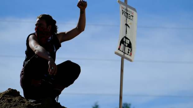 A lone water protector raises his fist in a solidarity salute with others who shut down an Enbridge Line 3 pumping station by occupying the site on Monday, June 7, 2021. (Photo by Mary Annette Pember, Indian Country Today)
