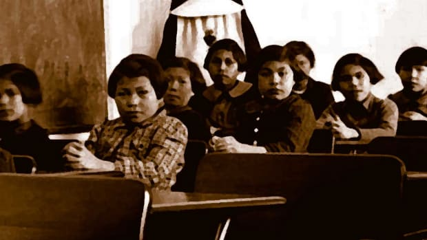 Pictured: A sepia photo of a residential school classroom.