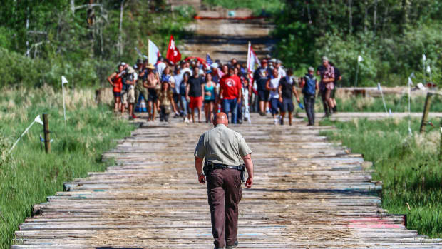 Clearwater County Sheriff Darin Halverson walks towards the Fire Light camp along the Mississippi River at an Enbridge Line 3 construction site on June 7, 2021, near Solway, Minnesota. Halverson was able to avoid mass arrests that occurred at other protest sites. (Photo courtesy of Line 3 Media Collective)