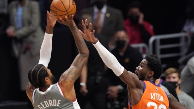Los Angeles Clippers guard Paul George, left, shoots as Phoenix Suns center Deandre Ayton defends during the first half in Game 4 of the NBA basketball Western Conference Finals Saturday, June 26, 2021, in Los Angeles. (AP Photo/Mark J. Terrill)