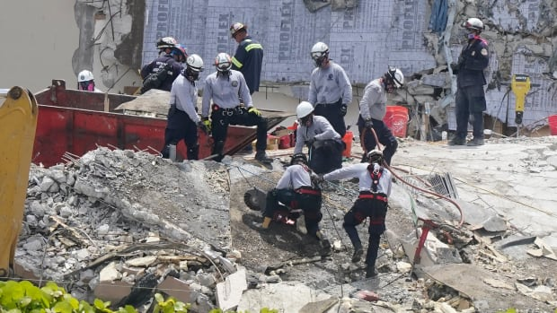 Workers cut a large slab of concrete at the Champlain Towers South condo, Monday, June 28, 2021, in Surfside, Florida as the search continues for survivors at the site of the collapsed building. At least 20 people have died as of Friday, July 2, 2021, and more than 100 were still missing. (AP Photo/Marta Lavandier)