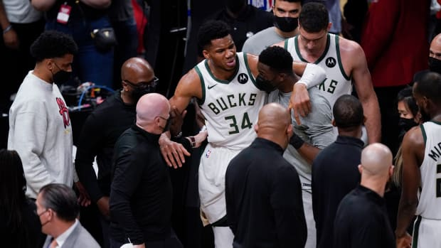 Milwaukee Bucks' Giannis Antetokounmpo (34) is helped off the court after he and Atlanta Hawks' Clint Capela fell during the second half of Game 4 of the NBA basketball Eastern Conference finals Tuesday, June 29, 2021, in Atlanta. (AP Photo/Brynn Anderson)