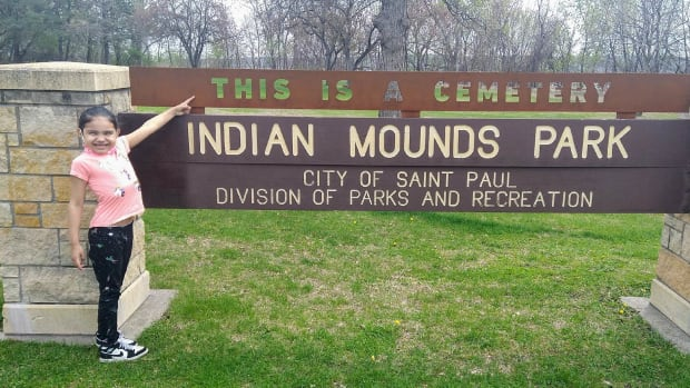 Crystal Norcross' daughter Kimimina Day posing in front of the new signage at Indian Mounds Park. (Photo courtesy of Crystal Norcross)