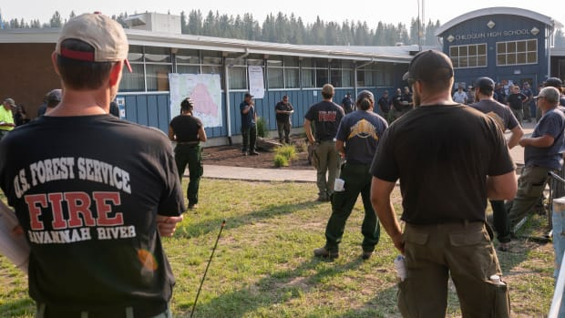 Firefighters from Oregon and other nationwide agencies meet at Chiloquin High School before heading toward the Bootleg Fire, Tuesday, July 13, 2021, in Chiloquin, Ore. (AP Photo/Nathan Howard)
