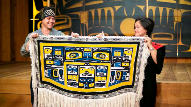 Lily Hope and Ricky Tagaban, both Tlingit, display the robe they collaborated to weave at its First Dance ceremony at the Sealaska Heritage Institute on June 22, 2020. (Photo Courtesy of Annie Bartholomew, The Juneau Empire)