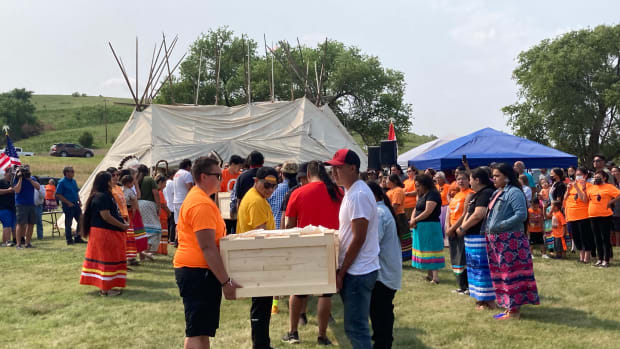 Young tribal members carried the remains of nine Sicangu children into a council teepee, where special prayers and ceremonies on July 16, 2021, marked their return home after more than 140 years. The children died after being forced to attend the Carlisle Industrial Indian School in Pennsylvania. (Photo by Vi Waln for Indian Country Today)