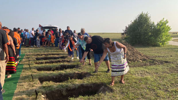 The Sicangu people paid their respects to six ancestors by putting a bit of earth into each of the small graves during a formal burial on July 17, 2021. The children died at Carlisle in the 1880s but did not return to their homelands on the Rosebud Indian Reservation for 140 years. (Photo by Vi Waln for Indian Country Today)