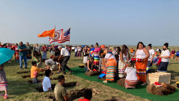 The Native American Women's Color Guard salutes as members of the Sicangu Youth Council help provide a formal burial on July 17, 2021, at the Rosebud Sioux Tribe Veteran's Cemetery for six ancestors who died at the Carlisle Indian Industrial School in the 1880s. The remains were finally returned to the homelands after 140 years, wrapped in buffalo robe bundles and placed in cedar boxes. (Photo by Vi Waln for Indian Country Today)