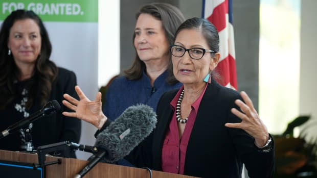 As Becky Mitchell, back left, and of the Colorado Water Conservation Board, and U.S. Rep Diana DeGette, D-Colo., look on, Interior Secretary Deb Haaland speaks during a news conference after Haaland's visit to talk about federal solutions to ease the effects of the drought at the offices of Denver Water Thursday, July 22, 2021, in Denver. Haaland will make stops in two cities on Colorado's Western Slope as part of her trip to assess the effects of the drought on the Centennial State. (AP Photo/David Zalubowski)