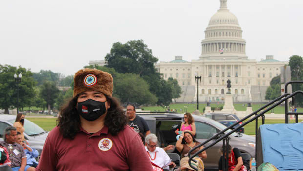 Individual wearing a mask and guarding the 25-foot totem pole at the Red Road to DC on the National Mall in Washington, D.C., on July 29, 2021. (Photo by Jourdan Bennett-Begaye, ICT)