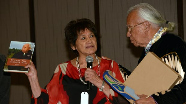 Lorraine Loomis, chairperson of the Northwest Indian Fisheries Commission, speaks with Billy Frank Jr. at his 83rd birthday party in 2014. Loomis spend more than 40 years as a fisheries commissioner, fighting for treaty fishing rights and salmon habitats, and replaced Frank as chair in 2014. Loomis died Aug. 10, 2021. Frank died in 2014. (Photo by Debbie Preston, courtesy of the Northwest Indian Fisheries Commission)