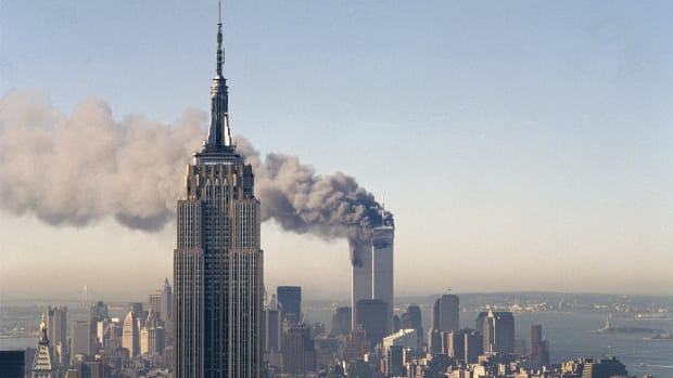 The twin towers of the World Trade Center burn behind the Empire State Building in New York, Sept. 11, 2001. In a horrific sequence of destruction, terrorists crashed two planes into the World Trade Center causing the twin 110-story towers to collapse. (AP Photo/Marty Lederhandler)