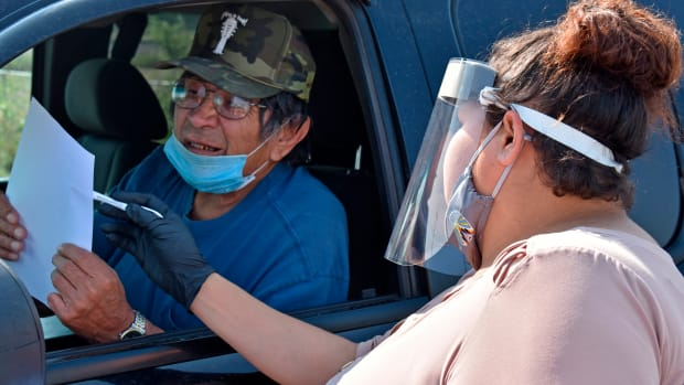 """FILE - IN THIS AUG. 26, 2020 FILE PHOTO, Selena Rides Horse speaks with Gerald Pease at a drive-thru station set up by Western Native Voice to help members of the Crow Indian Tribe participate in the U.S. Census in Lodge Grass, Mont. Native Americans make up less than 2% of the U.S. population and often are listed in datasets as """"other"""" or denoted with an asterisk. Even when surveyed, the results can be considered statistically insignificant because the sample size isn't large enough or the margin of error is too great to accurately reflect the population. The National Congress of American Indians has said there's a critical need for data that is accurate, meaningful and timely within tribal communities. (AP Photo/Matthew Brown, File)"""