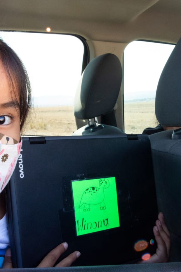 Second-grader Winona Begaye uploads homework in her family's vehicle near Piñon. Navajo Nation schools have remained virtual this fall because it's too dangerous to reopen their doors. To help families with no internet or poor access get online, the Piñon Unified School District outfitted school buses with Wi-Fi. (Photo by Megan Marples/Cronkite News)