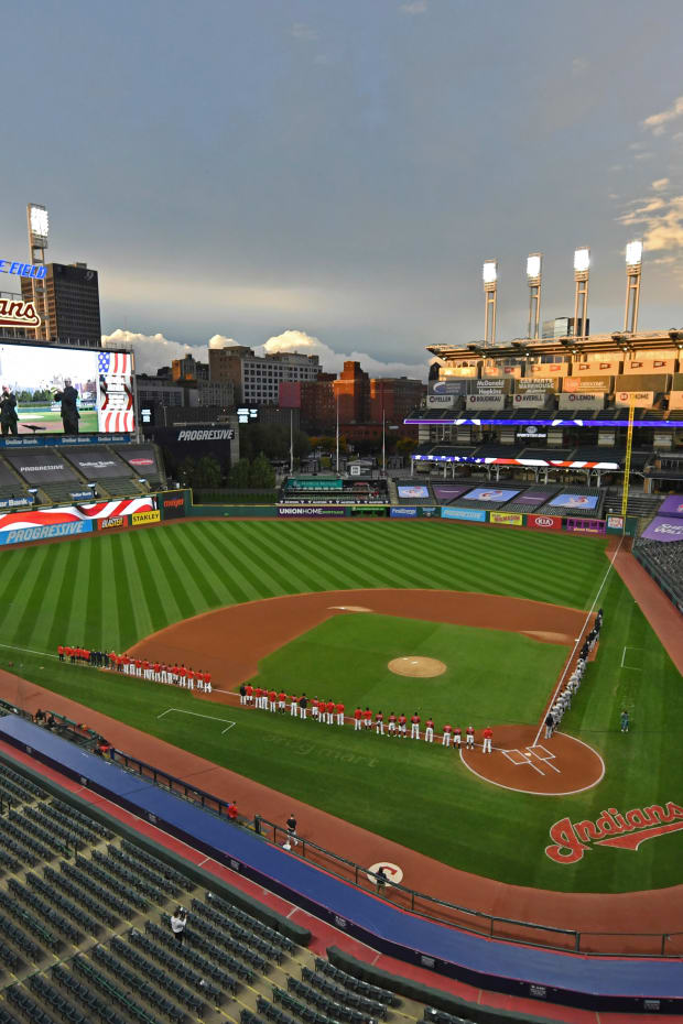 FILE - In this Sept. 29, 2020, file photo, players and coaches for the New York Yankees and the Cleveland Baseball Team stand for the national anthem before Game 1 of an American League wild-card baseball series in Cleveland. The Indians are changing their name after 105 years, a person familiar with the decision told The Associated Press on Sunday, Dec. 13, 2020. After months of internal discussion prompted by public pressure and a national movement to remove racist names and symbols, the team is moving away from the name it has been called since 1915, said the person who spoke on condition of anonymity because the team has not revealed its plans. (AP Photo/David Dermer, File)
