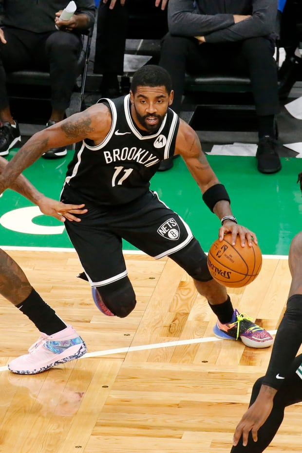 Brooklyn Nets guard Kyrie Irving (11) drives past Boston Celtics guard Marcus Smart as teammate DeAndre Jordan sets a pick during the first half of an NBA preseason basketball game, Friday, Dec. 18, 2020, in Boston. (AP Photo/Mary Schwalm)