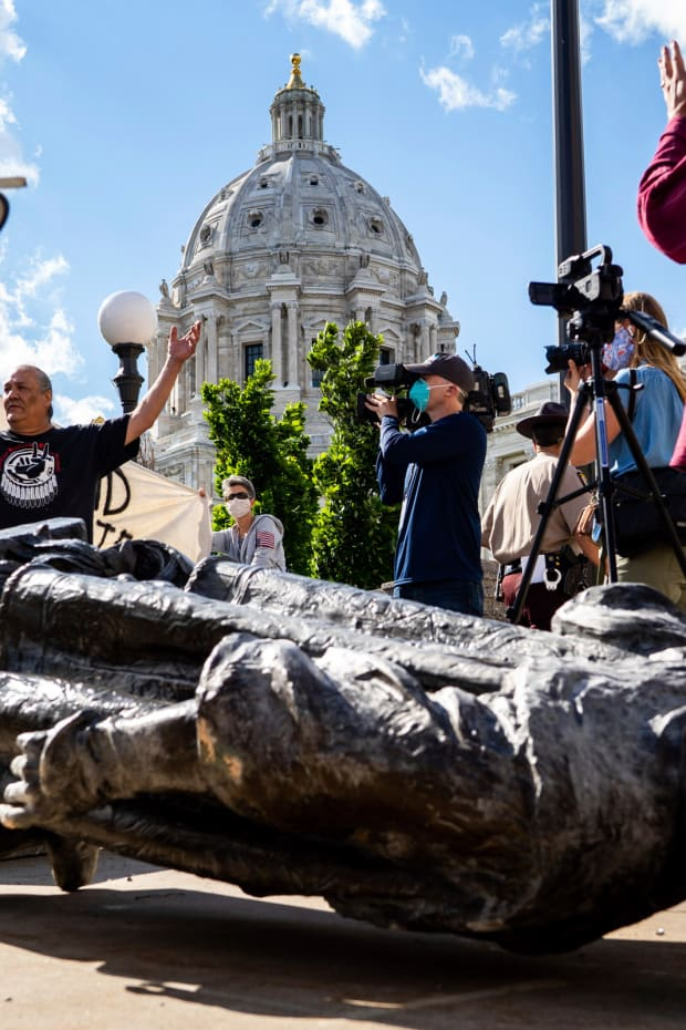 Mike Forcia raises his hands in the air as people photograph the fallen Christopher Columbus statue at the Minnesota state Capitol in St. Paul, Minn., Wednesday, June 10, 2020. (Evan Frost/Minnesota Public Radio via AP)