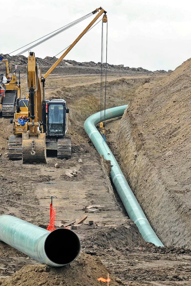 In this Oct. 5, 2016, file photo, heavy equipment is seen at a site where sections of the Dakota Access pipeline were being buried near the town of St. Anthony in Morton County, N.D. The Texas-based developer of the Dakota Access oil pipeline says it has complied with terms of a 2017 agreement settling allegations it violated North Dakota rules during construction, though state regulators are seeking more information. Energy Transfer Partners was accused of removing too many trees and improperly handling a pipeline route change after discovering Native American artifacts. (Tom Stromme/The Bismarck Tribune via AP, File)