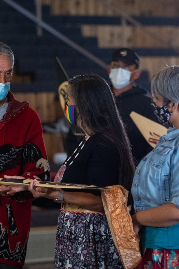 Steve Solomon of the Lummi Nation presents Shelly Boyd, middle, and the Confederated Tribes of the Colville Reservation with a gift of alliance between their Tribal Nations. Joined by her daughter Stevey Seymour, right, the members of the Sinixt/Arrow Lake band of the Confederated Tribes of the Colville Reservation spoke at the Indigenous Peoples Day celebration hosted by the Children of the Setting Sun Productions at the Wex'liem Community Building in Lummi Nation near Bellingham, Wash., Monday, Oct. 11, 2021. The event, streamed via Zoom and Facebook, highlighted the contributions and diverse cultures of Indigenous peoples as well as the need for climate action. (Photo by The Bellingham Herald)