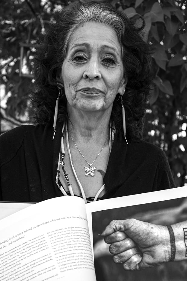 """LaDonna Tamakawastewin Allard in June 2019 at her home holding the photography book, """"Standing for Unity: The Standing Rock Movement,"""" by Eugene Tapahe. Tapahe presented her with the book, she was one of the contributors. (Photo by Eugene Tapahe, Tapahe Photography)"""