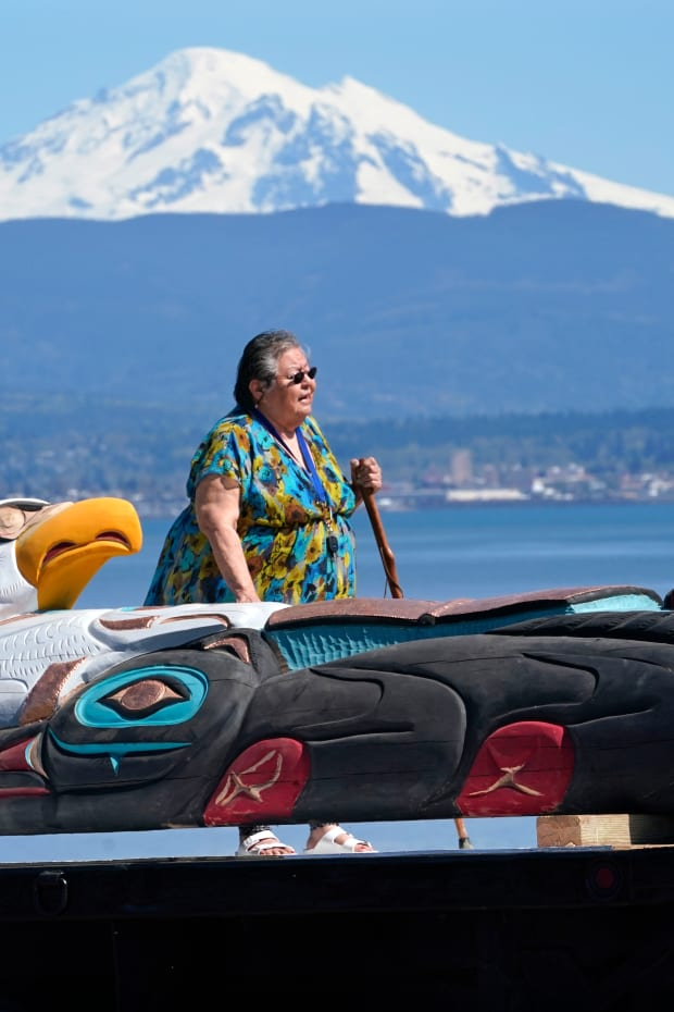 Lummi Nation elder Lucille Spencer prays over a nearly 25-foot totem pole, to be gifted from the tribe to the administration of President Joe Biden, in view of Mount Baker, background, shortly after the pole was moved from a carving shed Monday, April 19, 2021, on the Lummi Reservation, near Bellingham, Wash. The pole, carved from a 400-year old red cedar, will make a journey from the reservation past sacred indigenous sites, before arriving in Washington, D.C., in early June. Organizers said that the totem pole is a reminder to leaders to honor the rights of Indigenous people and their sacred sites. (AP Photo/Elaine Thompson)