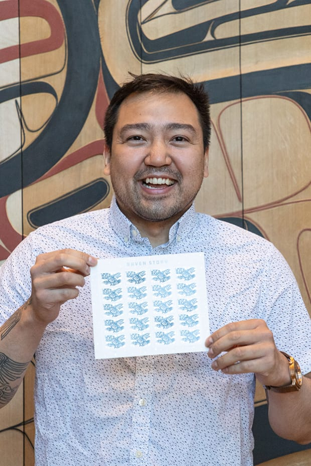 """Pictured: Rico Worl holding a sheet of """"Raven Story"""" stamps."""