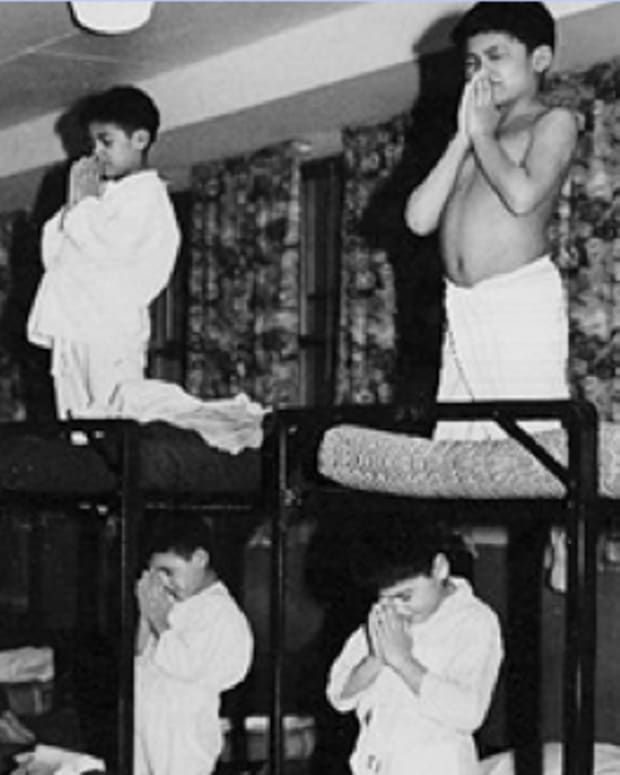 Residential school children students in a typical dormitory. Indigenous children forced to pray at the foot of their mattresses prior to being permitted to sleep, coldly watched by the overseer — a Nun acting as disciplinarian and enforcer. Taken in 1950 at the Bishop Horden Memorial School, a residential school in the Indigenous Cree community of Moose Factory, Ontario, Canada. (Source: CNS photo/Shingwauk Residential Schools Centre, Handout via Reuters)