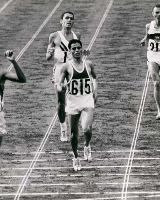 Billy Mills, Lakota, breaks the tape in the 10,000-meter run to take gold in the 1964 Olympics. (Official Marine Corps Photo}