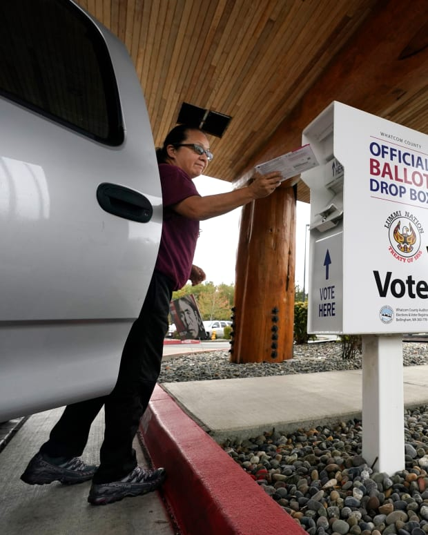 """Lummi Nation tribal member Karen Scott drops her completed ballot into a ballot drop box Monday, Oct. 19, 2020, on the Lummi Reservation, near Bellingham, Wash. Washington Native Vote Day is Tuesday, Oct. 20, where tribes throughout the state connect, mainly remotely this year because of the coronavirus, with each other to encourage tribal members to register to vote and to cast their ballots. The historic photo used on the voting poster is referred to as """"Lummi Woman,"""" shot by Edward Curtis in 1899. It wasn't until 1962 that every state in the nation secured the right to vote for Native people. (AP Photo/Elaine Thompson)"""