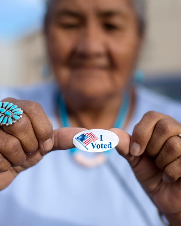 "FILE - In this Aug. 28, 2018 file photo, Mildred James of Sanders, Ariz., shows off her ""I Voted"" sticker as she waits for results of the Navajo Nation presidential primary election to be revealed in Window Rock, Ariz. The Navajo Nation is suing Arizona counties over what it says were unequal opportunities for tribal members to correct signature deficiencies on early ballots in Arizona's general election. The tribe is asking a federal judge in a lawsuit filed this week to allow more than 100 Navajos to make the fixes. The request has the potential to delay the state's certification of ballots, scheduled for Dec. 3. (AP Photo/Cayla Nimmo, File)"