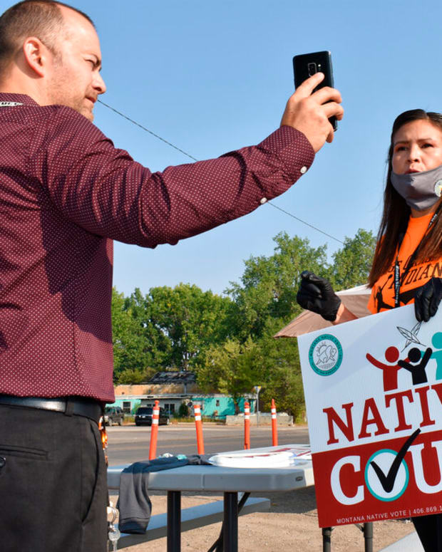 """FILE - In this Aug. 26, 2020 file photo, activist Lauri Dawn Kindness, right, speaks at the Crow Indian Reservation, in Lodge Grass, Mont. Native Americans make up less than 2% of the U.S. population and often are listed in datasets as """"other"""" or denoted with an asterisk. Even when surveyed, the results can be considered statistically insignificant because the sample size isn't large enough or the margin of error is too great to accurately reflect the population. The National Congress of American Indians has said there's a critical need for data that is accurate, meaningful, and timely within tribal communities. (AP Photo/Matthew Brown, File)"""