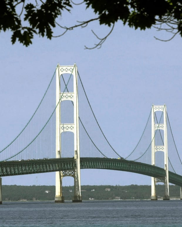 This July 19, 2002, file photo, shows the Mackinac Bridge that spans the Straits of Mackinac from Mackinaw City, Michigan. Supporters and opponents of a proposed oil pipeline tunnel beneath the Great Lakes channel are making their case to federal officials. The Army Corps of Engineers hosted an online public hearing Monday, Jan. 11, 2021, on Enbridge's application for a permit. The Canadian pipeline company wants to drill a nearly 4-mile (6.4-kilometer) tunnel through bedrock under the Straits of Mackinac that would house a replacement for twin pipes that have run along the bottom of the waterway connecting Lake Huron and Lake Michigan for 67 years.(AP Photo/Carlos Osorio, File)