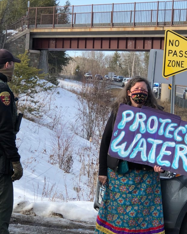 "Carrie Chesnik of Oneida Nation holds a ""Protect Water"" sign as part of the march to observe the 30th anniversary of the 1991 spill into the Prairie River and was charged with public nuisance and obstructing a roadway on March 3, 2021. (Photo by Mary Annette Pember, Indian Country Today)"