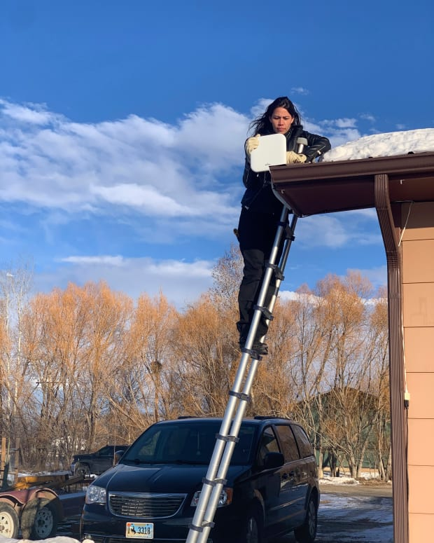 In this photo provided by Mariel Triggs and taken Jan. 17, 2020, Mariel Triggs, chief executive of MuralNet, tests broadband internet equipment in Fort Washakie on the Wind River Indian Reservation in Wyoming. (Patrick Lawson via AP)