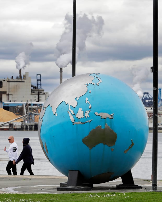 In this April 21, 2020 photo, people walk past an Earth globe sculpture at Thea's Park in Tacoma, Wash., with the WestRock Paper Mill in the background. Wednesday is the 50th anniversary of Earth Day, and observance that helped spur activism against air and water pollution and disappearing plants and animals, but ongoing challenges remain throughout the world. (AP Photo/Ted S. Warren)