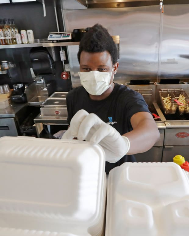 Falafel shop employee Javohn Ferguson works to pack a customer's take-out order in a restaurant otherwise closed because of the coronavirus outbreak Tuesday, May 19, 2020, in Seattle. Washington state Gov. Jay Inslee on Tuesday announced $10 million in grants to small businesses in industries particularly hard-hit by the COVID-19 outbreak. They include restaurants, hair salons, fitness studios and theaters. (AP Photo/Elaine Thompson)