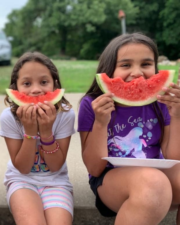 Kim Duncan's three adopted daughters, from left, Shalyn, Shyanne and Shelbi, sit smiling with their watermelon in the summer heat, September 2021. (Courtesy photo)