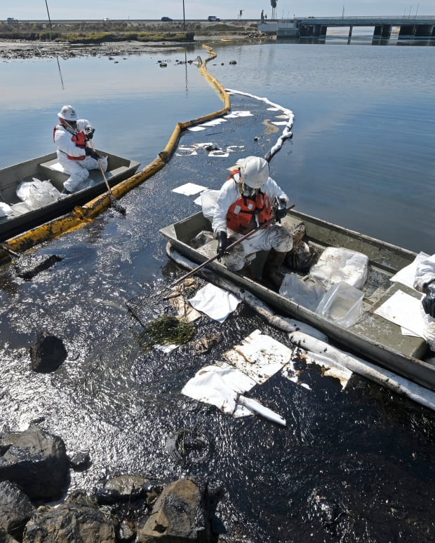 Cleanup contractors deploy skimmers and floating barriers known as booms to try to stop further oil crude incursion into the Wetlands Talbert Marsh in Huntington Beach, Calif., Sunday, Oct. 3, 2021. One of the largest oil spills in recent Southern California history fouled popular beaches and killed wildlife while crews scrambled Sunday to contain the crude before it spread further into protected wetlands. (AP Photo/Ringo H.W. Chiu)