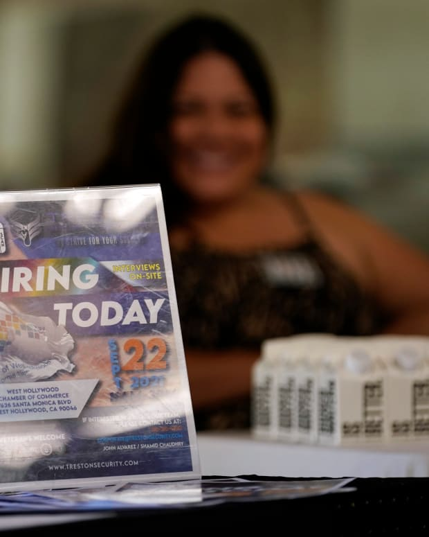 FILE - In this Sept. 22, 2021 file photo, a hiring sign is placed at a booth for prospective employers during a job fair in the West Hollywood section of Los Angeles. U.S. job growth slowed sharply last month as the highly contagious delta variant disrupted economic activity and employers struggled to find workers. (AP Photo/Marcio Jose Sanchez)