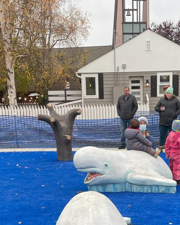 """One of the Alaska Native elements in a renovated downtown playground at 538 W. 10th Ave. in Anchorage, is the """"yuyqul"""", or spearing tree. A replica is shown left of center in this photo. The yuyqul was a tree placed upside down in Cook Inlet's mud flats for use by the Dena'ina Athabascan people to hunt Beluga whales. The Anchorage Municipality and Anchorage Parks Foundation held a grand opening of the revamped park on Oct. 11, 2021 (Photo by Joaqlin Estus)"""