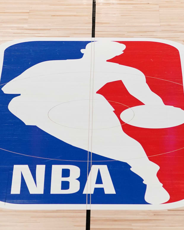 """FILE - The NBA logo in shown on a basketball court in Lake Buena Vista, Fla., in this Friday, Aug. 28, 2020, file photo. Pacers coach Rick Carlisle says his new team has a """"very high"""" vaccination rate but declined to give a specific number because of privacy concerns. He did say Monday during NBA media day that all members of the Indiana coaching staff are fully vaccinated. Carlisle is back in Indiana, where he coached from 2003 through 2007. Training camps open Tuesday and the pandemic will affect a third NBA season and already means some players will be missing on media day.(AP Photo/Ashley Landis, Pool, File)"""